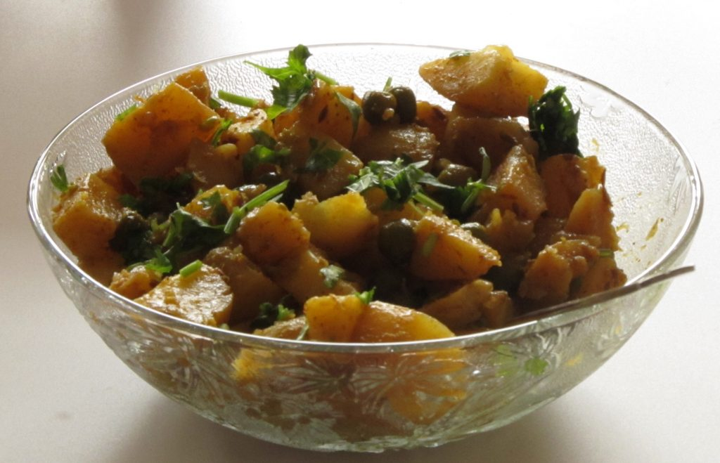 Glass bowl with potato and peas curry