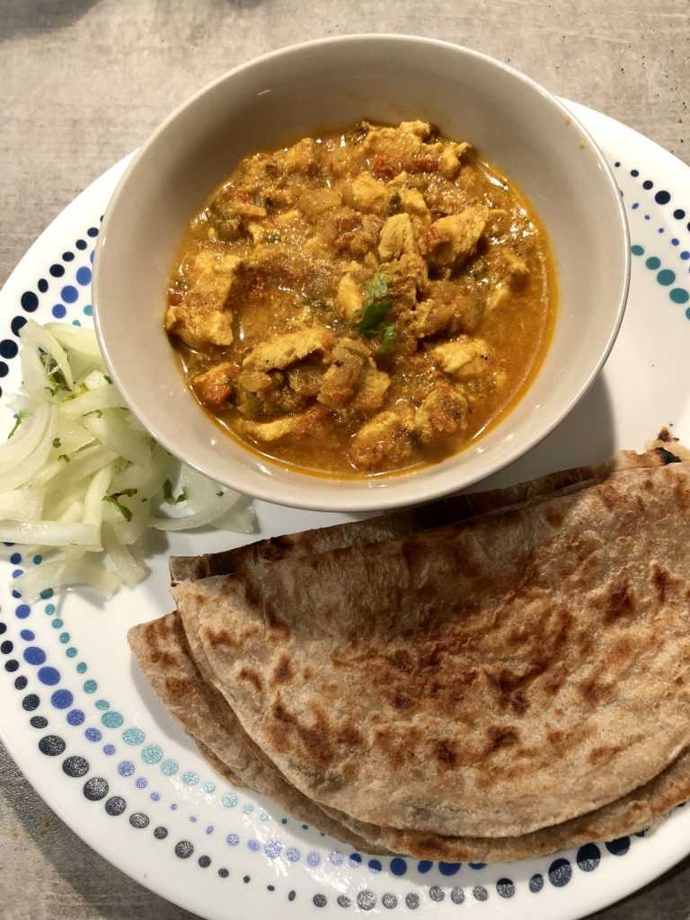 Chicken curry served with sliced onions and rotis
