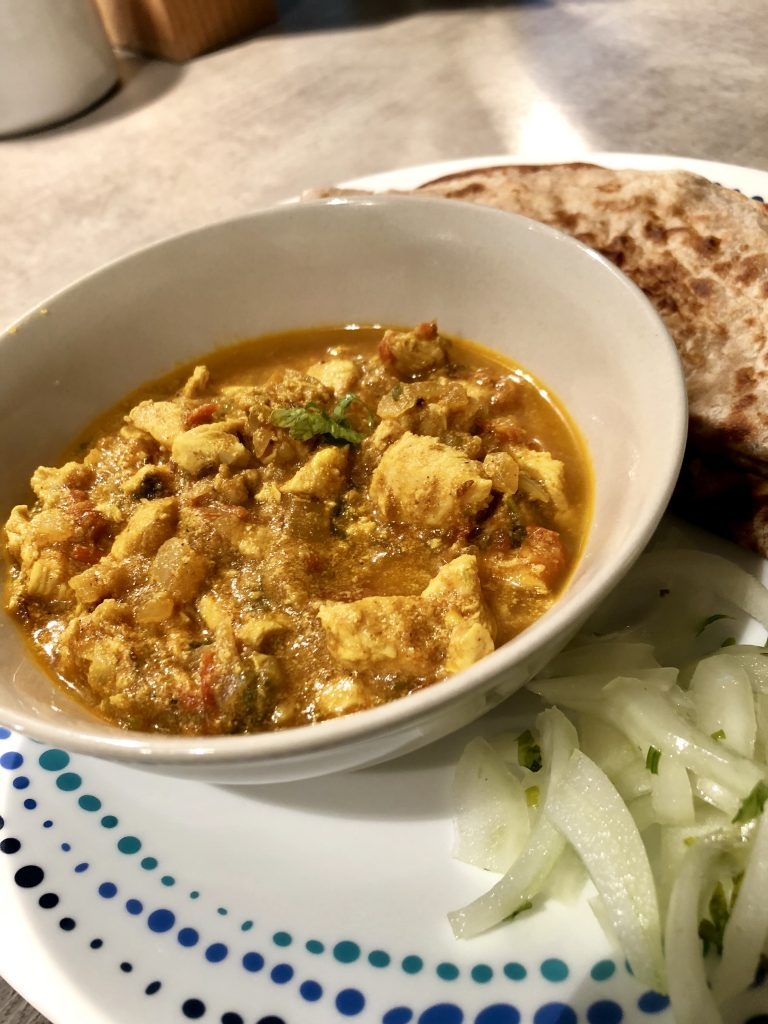 Chicken curry in a bowl served with rotis
