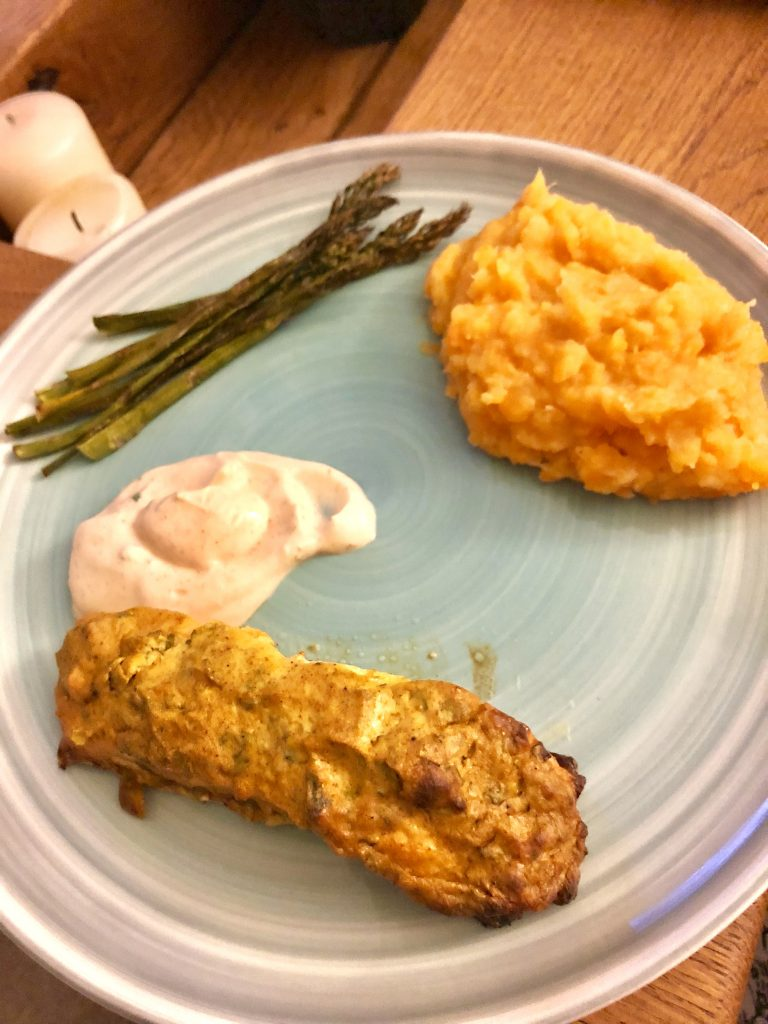 Green plate with tandoori salmon, dip, mash and asparagus