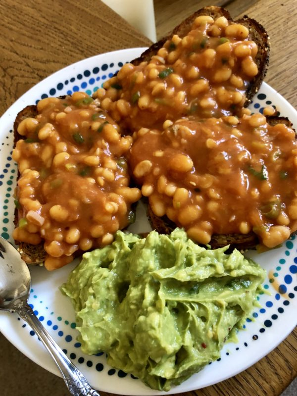 White plate with masala baked beans on toast with smashed avocados