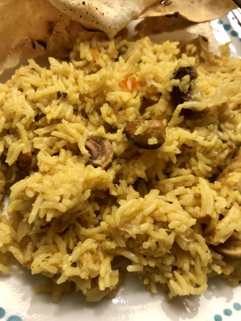 Yellow coloured tomato coriander spiced rice on a plate