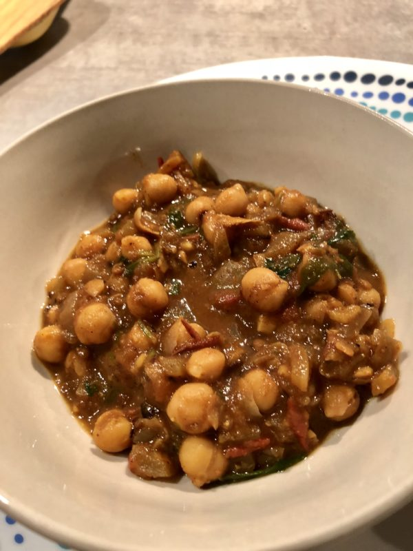Chlole or chickpeas curry in a tomatoey curry served in a white bowl alongside roti