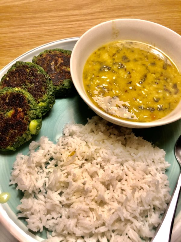 Palak dal served alongside white rice and spinach and potato cutlets on a green dish