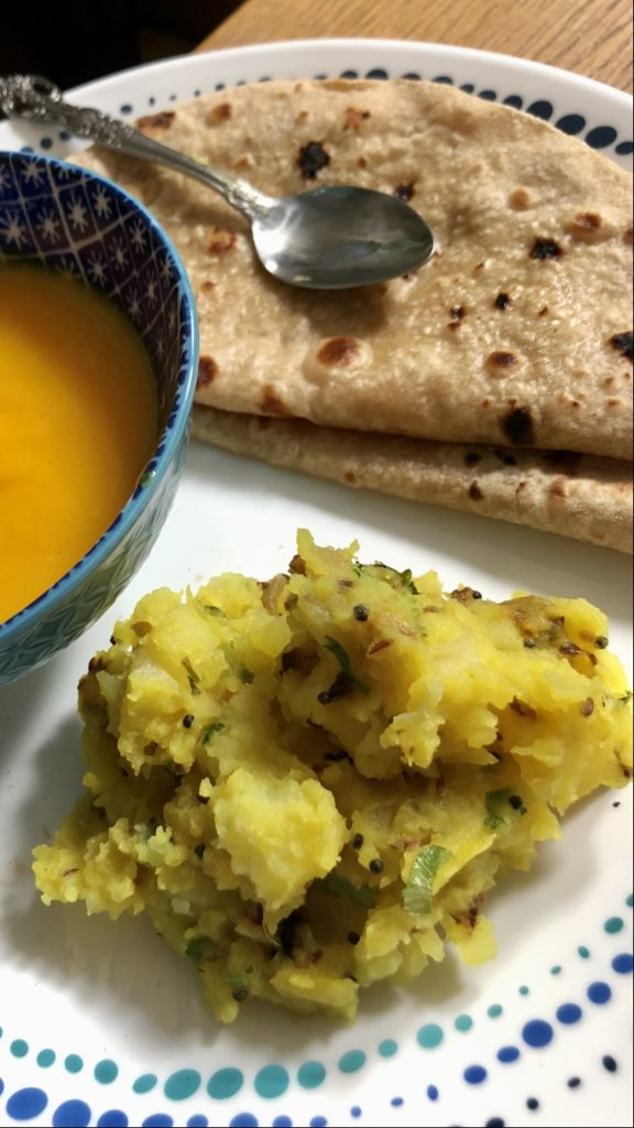 Picnic potatoes with aam was ( mango puree) and rotis on a white plate