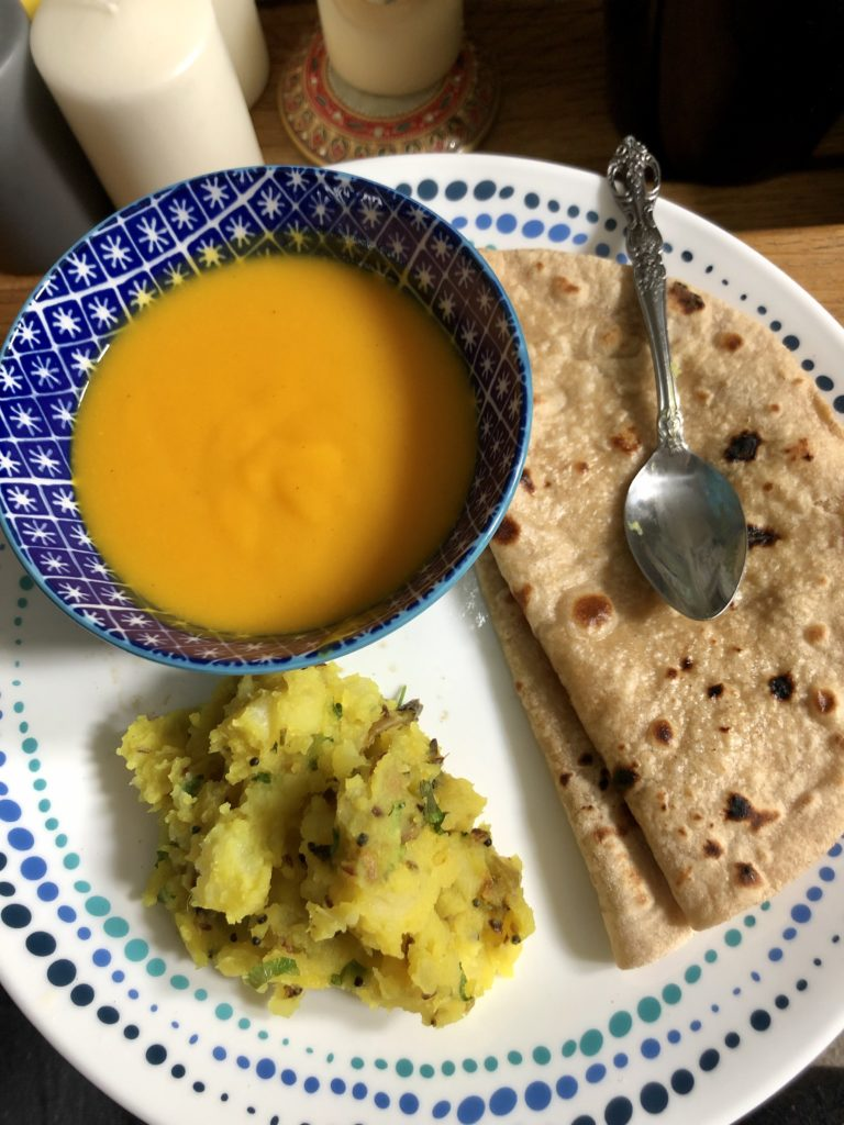 White dish with a blue bowl full of yellow mango pulp , rotis and potatoes