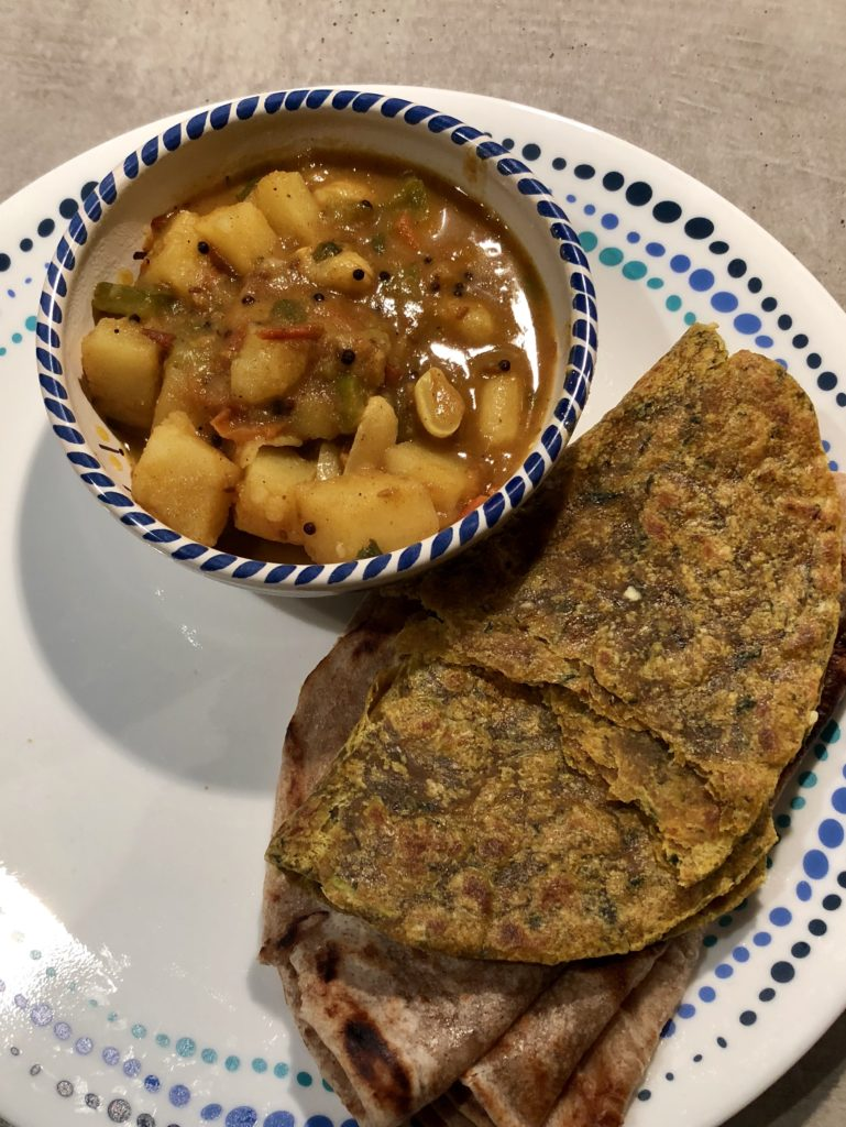 Potato curry in a bowl alongwith rotis on a white plate