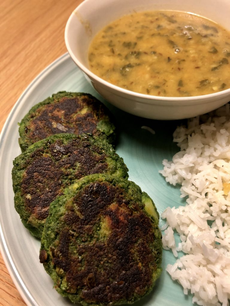2 Hara bhara kebabs on a green plate with white rice and dal