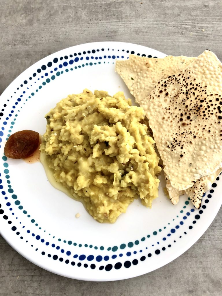 Dal khichdi on a white plate with poppadoms and pickle