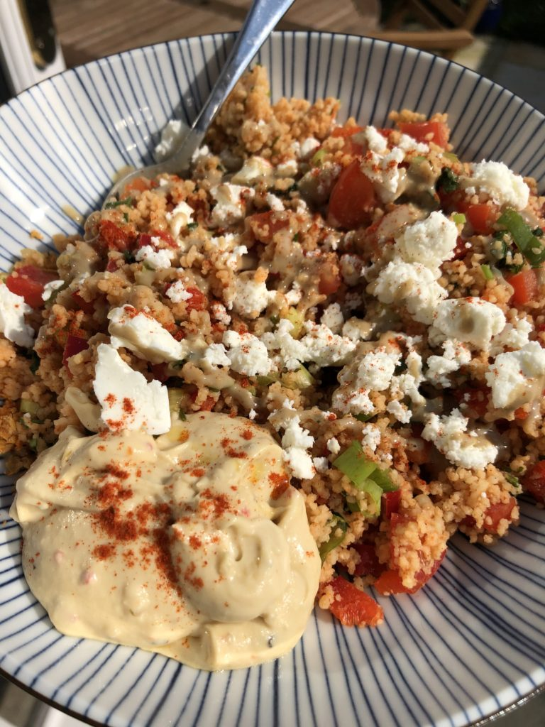 Blue striped bowl with couscous and veggies topped with feta cheese and hummus
