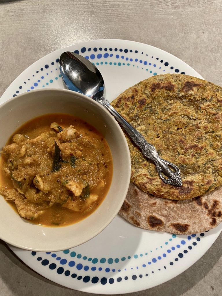 Dish with a bowl with chicken ka Salan - a curry made with coconut, peanuts, sesame and tamarind and rotis