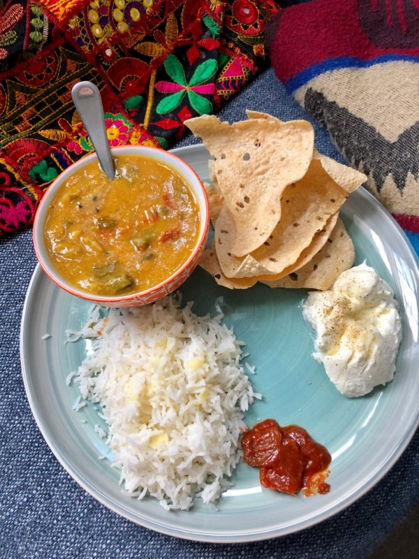 Green dish with sambar - lentil and veggie stew - served alongside rice, poppadoms, yogurt and lemon pickle