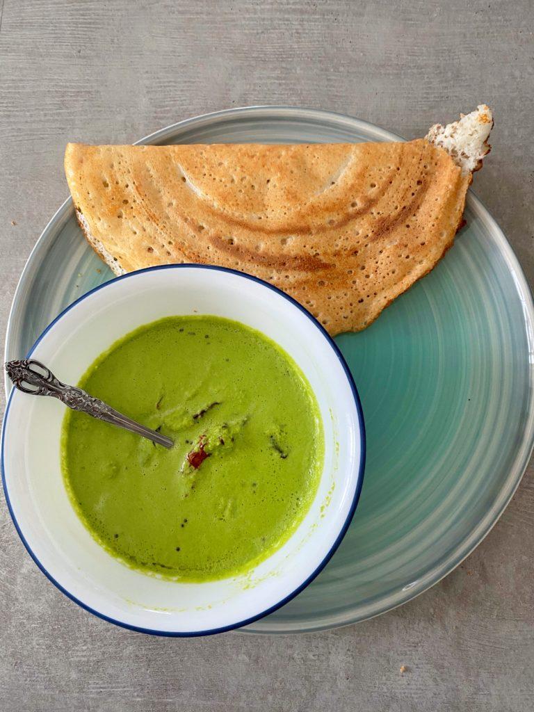 Coconut coriander chutney served alongside dosa on a green dish