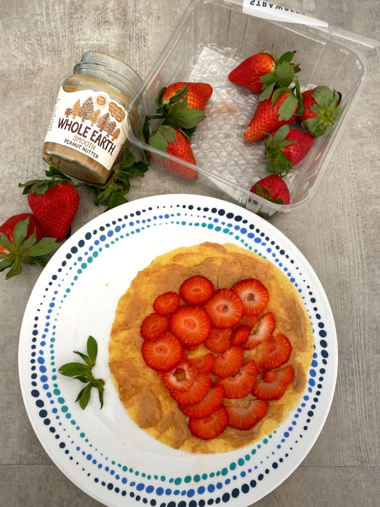Corn wrap with peanut butter and strawberry slices alongside a peanut butter bottle and a punnet of strawberries