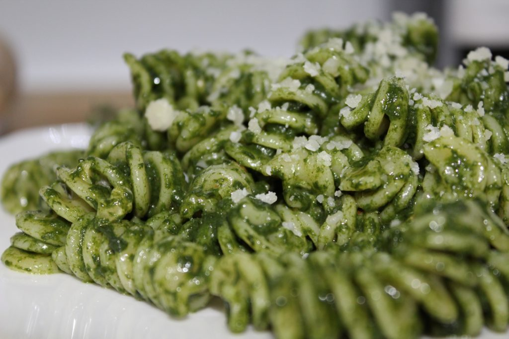 Fusilli with pesto sprinkled with Parmesan cheese