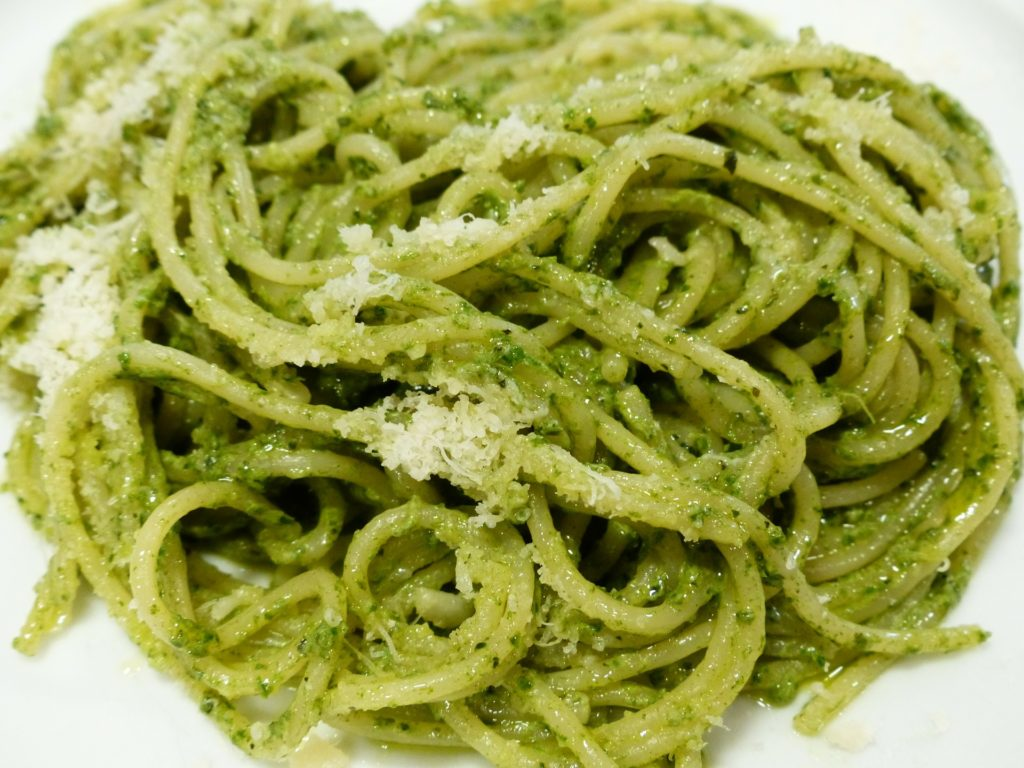 Spaghetti with a pesto sauce topped with grated parmesan