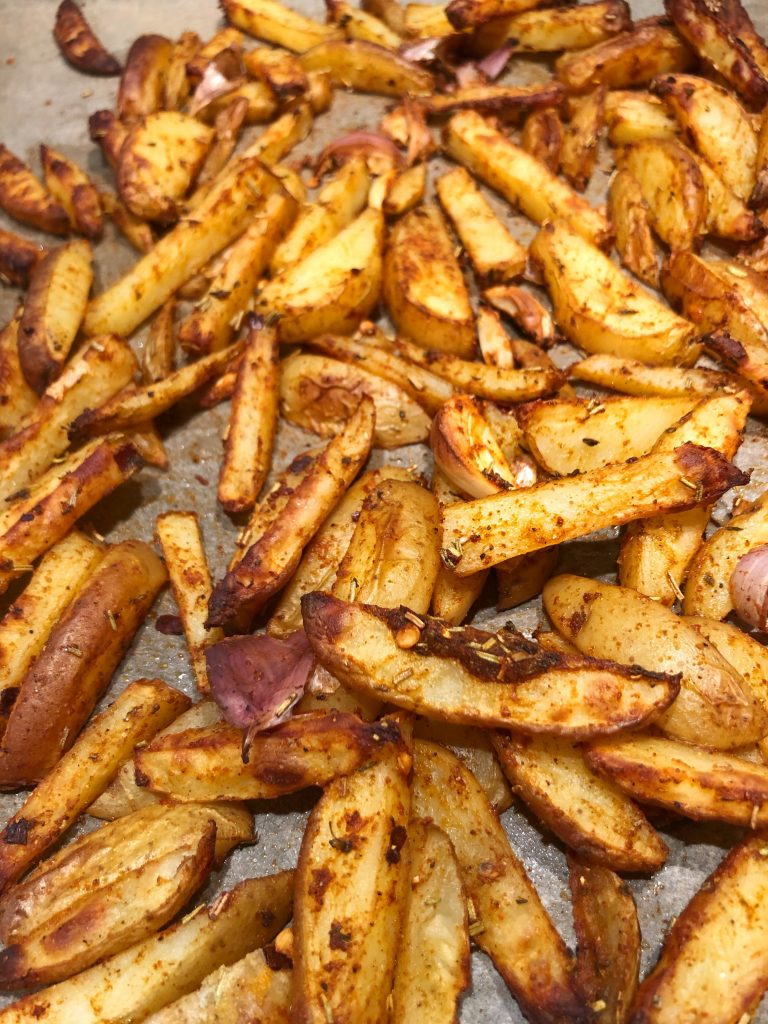 Baked potatoes wedges with seasoning of rosemary, thyme and garlic