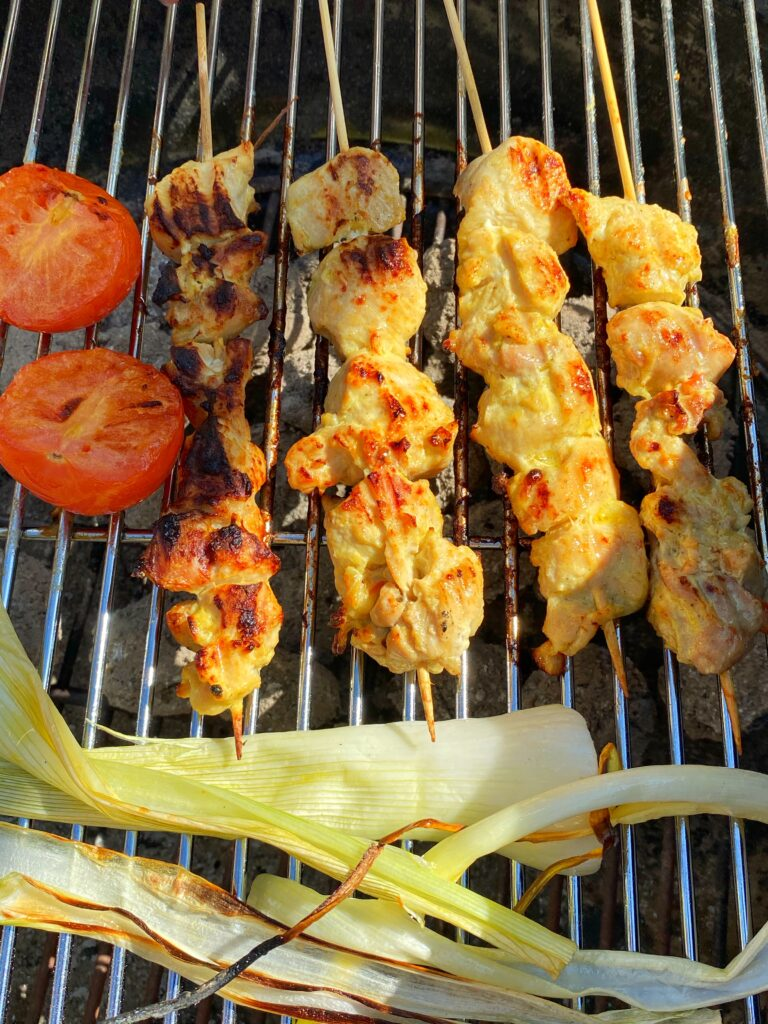 Jujeh kebab or Persian saffron chicken skewers with tomatoes and spring onions grilling over charcoal