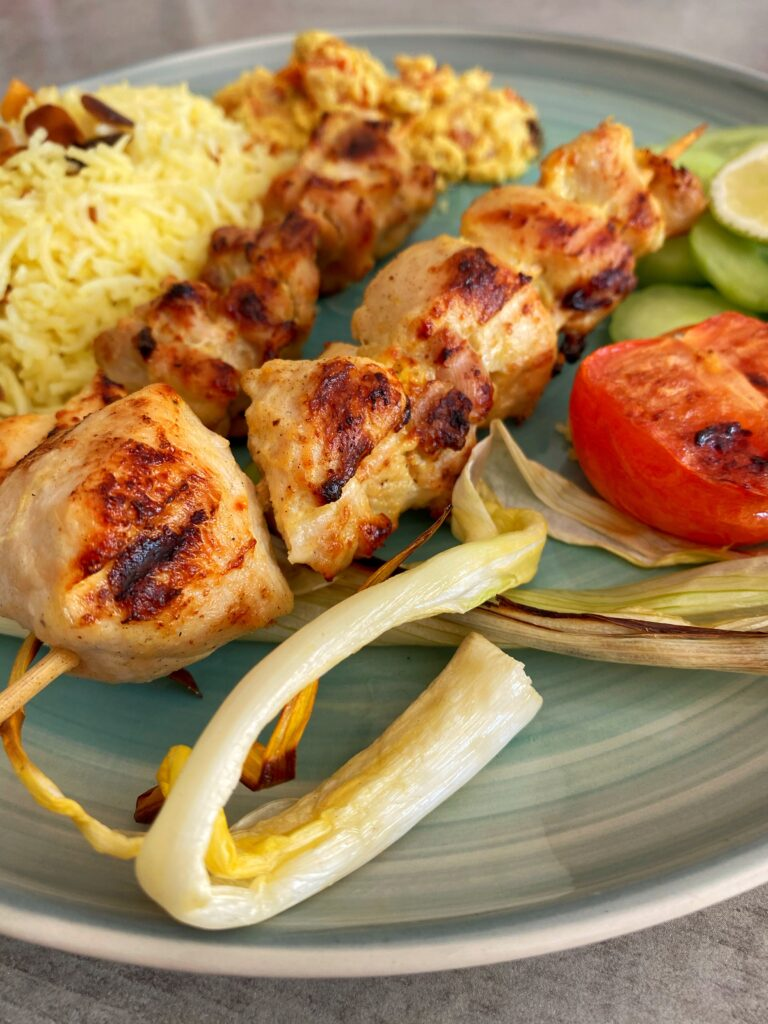 Jujeh kebab or Persian saffron chicken skewers served alongside saffron rice, cucumber slices and grilled tomatoes and spring onions